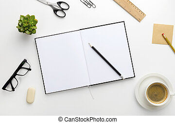 Top view of white office desk with notebook and supplies