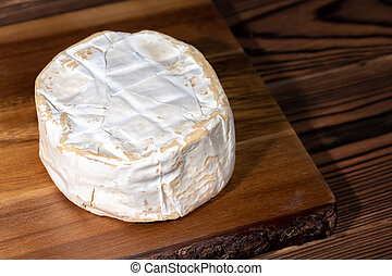 top view of whole white cheese with mold on wooden background