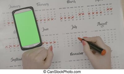 Top view of woman hands crossing calendar days planning to...