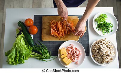 Top view of woman hands cutting vegetables on a wooden board...