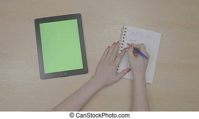 Top view of woman hands planning shopping list for vacation with green screen tablet pc and writing on notepad