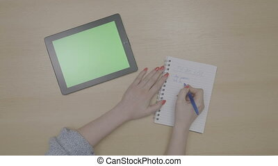Top view of woman hands planning to do list with green screen tablet pc and writing on notepad