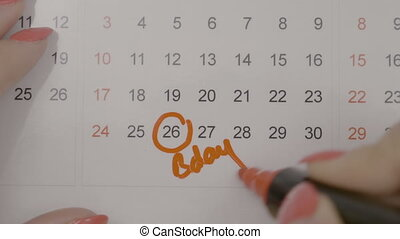 Top view of woman hands signing birth day on calendar and...