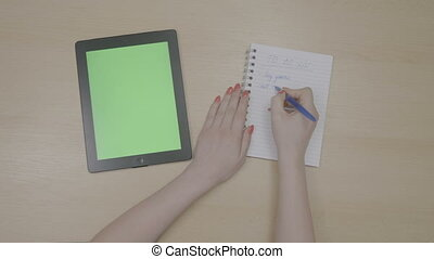 Top view of woman hands with red nails having free time and planning a to do list with green screen tablet pc and writing on notebook
