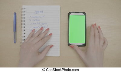 Top view of woman hands with red nails touching smartphone with green screen and looking at notepad list with recipe ingredients