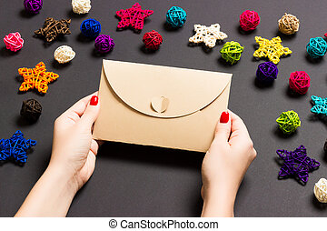 Top view of woman holding an envelope on black background made of holiday decorations. Christmas time concept