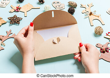 Top view of woman holding an envelope on blue background made of holiday decorations. Christmas time concept