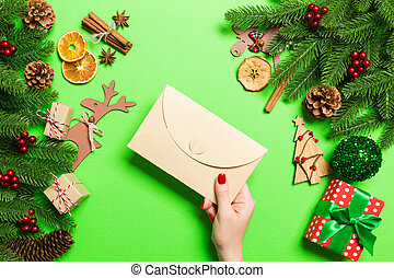 Top view of woman holding an envelope on green background made of holiday decorations. Christmas time concept
