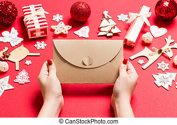 Top view of woman holding an envelope on red background made of holiday decorations. Christmas time concept