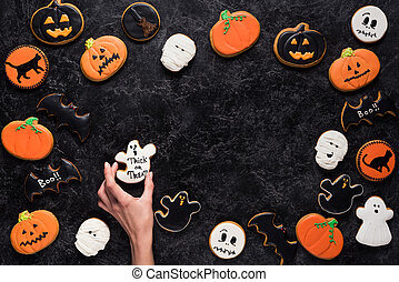 woman holding halloween cookie