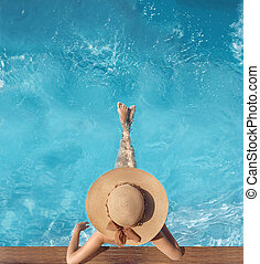 Top view of woman in straw hat relaxing in swimming pool at...
