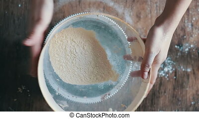 Top view of woman sieving flour in plate