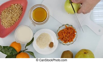Top view of woman's hands cuted an apple on chopping board in a kitchen. cooking healthy food