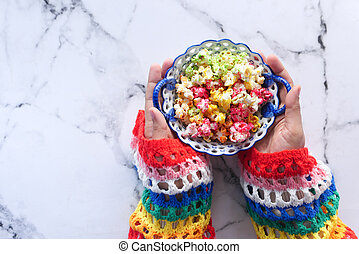 top view of women hand holding a bowl of colorful popcorn