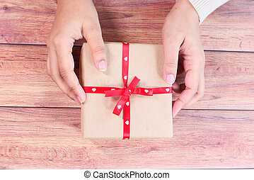 top view of women hand holding a gift box on table