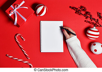 Top view of women hand writing in blank notebook with gift box and party decorations on red background.