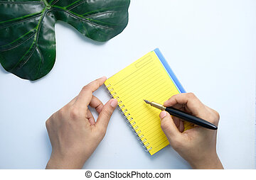 top view of women hand writing on notepad on white background