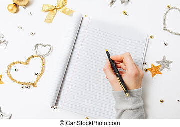 Top view of women writing a goal to make a list for the new year or Christmas on a notebook, Christmas decoration.