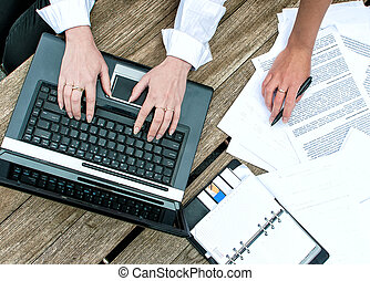 Top view of women's hands with documents and laptop