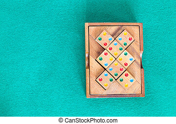 top view of wooden box with puzzle on green table - top view...