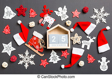 Top view of wooden calendar. The twenty fifth of December. New Year decorations on black background. Merry Christmas concept