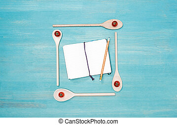 Top view of wooden spoons with cherry tomatoes and blank open cookbook with pencil on table