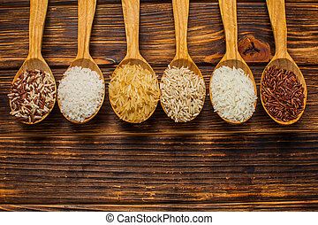 Top view of wooden spoons with different rice types