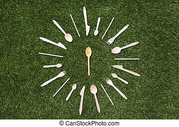 top view of wooden spoons with forks and knives on grass