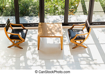 Top view of wooden table and chairs in coffee shop next to window in sunlight.