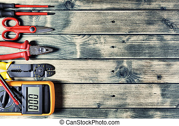 Top view of work tools for electrical installation on rustic wooden background