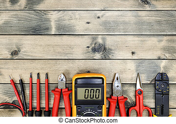 Top view of work tools for residential electrical installation on antique wooden background.