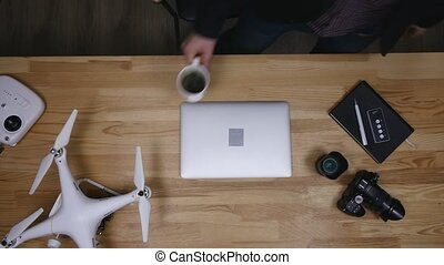 Top view of workplace photographer. A man working at the computer and drinking coffee. The items are laid out in the spirit of perfectionism on a wooden background
