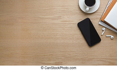 Top view of workspace with smartphone, copy space, coffee cup and office supplies on wooden table
