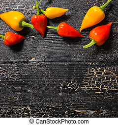 top view of yellow and red hot chili peppers on cracks black background, close up