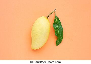 Top view of yellow mango on orange background.