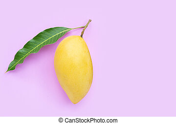 Top view of yellow mango on pink background.