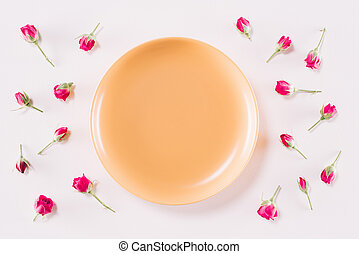 top view of yellow plate and scattered roses isolated on white, valentines day concept