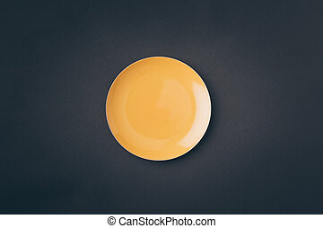 top view of yellow plate on gray table
