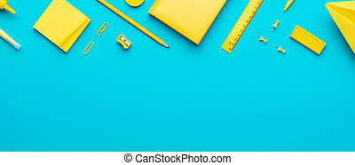 Top view of yellow stationery over turquoise blue background with copy space