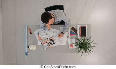 Top view of Young architect working at office desk calling by smartphone