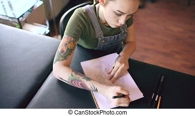 Top view of young attractive red haired woman tattoo artist sitting at table and creating sketch for tattooing in studio indoors