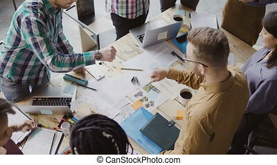 Top view of young business team working together near the table, brainstorming. Two mans fist greeting each other.