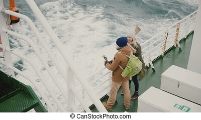 Top view of young couple standing on the board of the ship....