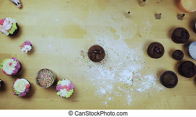 Top view of young female hands decorating the chocolate cupcake or muffin with cream, using pastry bag for this.