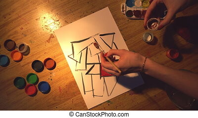 top view of young girl artist create an illustration with watercolor paints on wooden floor