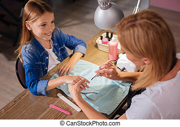 Top view of young manicurist cutting girls nails with scissors