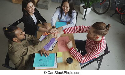 Top view of young multi-ethnic team crossing hands together after successful agreement about new project in modern loft office