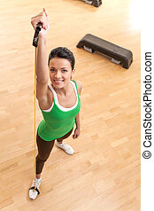 top view of young pretty fit woman exercising. woman with elastic fitness band looking up