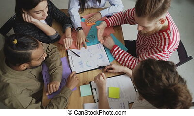 Top view of young team of male and female business colleagues watching and discussing new start-up project charts in modern loft office