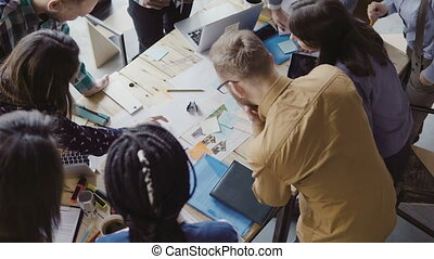 Top view of young team working on new project. Group of mixed race people standing near the table and discussing.